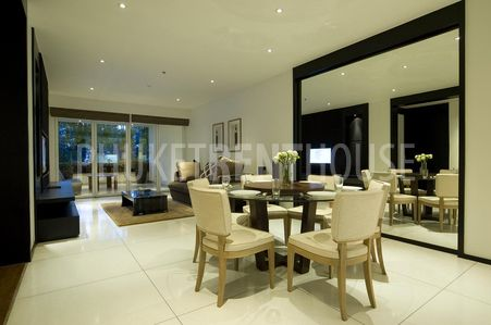 An open planned dining room with living room and kitchen. Spacious design, decorated beautifully.
