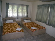Upstairs Second bedroom.Twin single beds. Aircon or windows on 3 sides. Wardrobe,and dressing table.