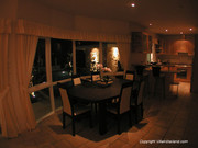 Night visual of dining area and kitchen.