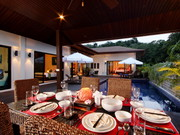 Tranquil outdoor dining adjacent to swimming pool
